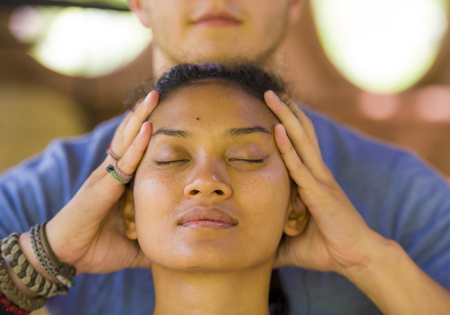 Photo pour natural lifestyle portrait of young beautiful and relaxed Asian Balinese woman receiving a healing facial and head Thai massage by male therapist at traditional spa in beauty wellness concept - image libre de droit