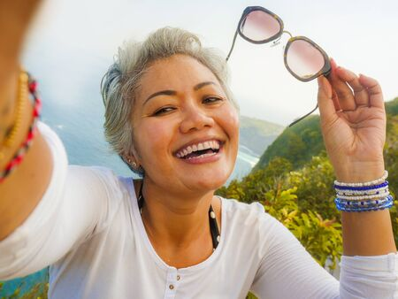 Photo for middle age 50s happy and cheerful Asian woman with grey hair taking selfie with mobile phone at beautiful tropical beach island smiling at cliff viewpoint enjoying Summer holidays travel destination - Royalty Free Image