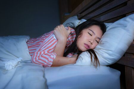 Foto de young beautiful sad and depressed Asian Chinese woman trembling in bed suffering cold and flu at night feeling unwell at night in her bedroom in health care and depression problem concept - Imagen libre de derechos