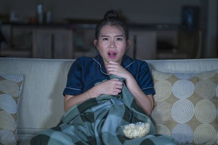 Photo pour young beautiful scared and frightened Asian Korean woman watching horror scary movie or thriller eating popcorn in fear face expression eating popcorn sitting at living room couch in the dark - image libre de droit