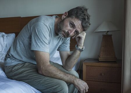 Photo pour Attractive depressed and upset man thoughtful at home bedroom . dramatic lifestyle portrait of handsome guy sitting on bed feeling sad thinking and suffering depression and anxiety problem - image libre de droit