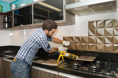 Photo pour Man renovating, renovating the kitchen, installing tile on the wall. - image libre de droit