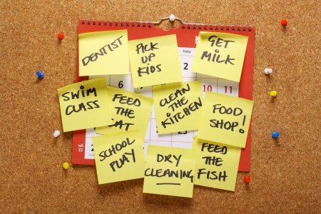 Photo pour A wall calendar on a cork notice board covered with yellow sticky paper notes as a reminder of household chores  - image libre de droit