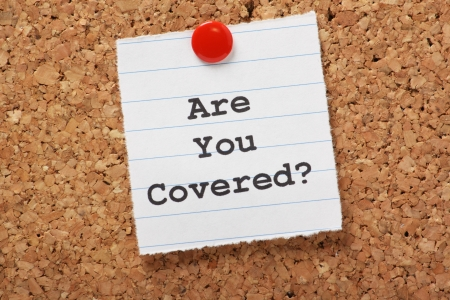 The words Are You Covered typed on a scrap of lined paper and pinned to a cork notice board Asking the question, are you insured for your car, travel, home or other liability