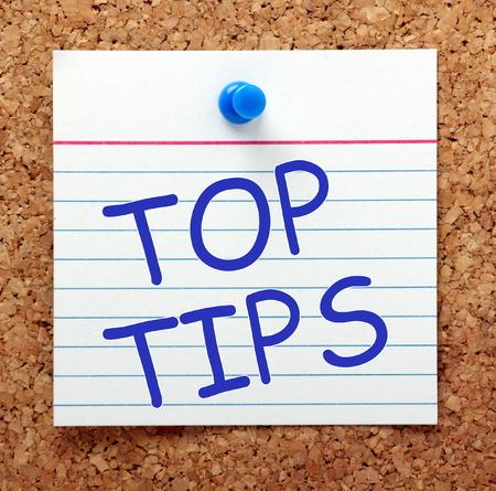 Foto de The phrase Top Tips in blue text on an index card pinned to a cork notice board as a reminder - Imagen libre de derechos