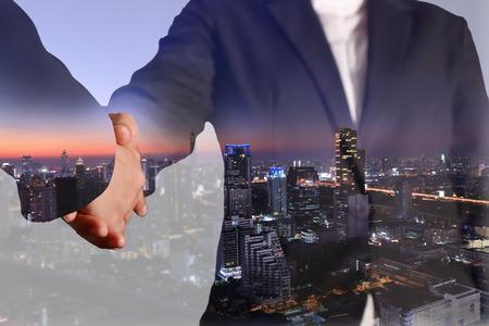 Photo pour Double exposure of handshake and night city, blue tone - image libre de droit