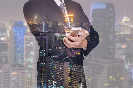 Double exposure of business man hand hold smart phone, mobile and night city as communication concept.