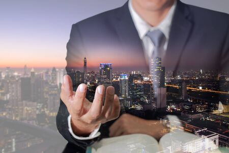 Double exposure of business man hand hold and night cityscape as everything in hand concept.