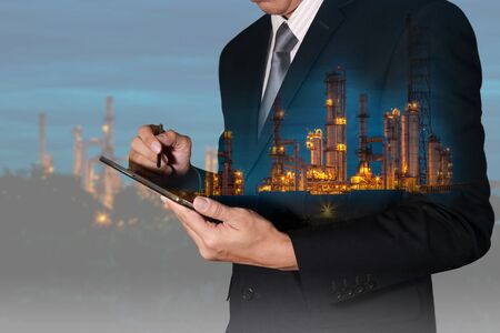 Double exposure of business man hand hold tablet and gas refinery industry factory in the night as Energy Research concept.
