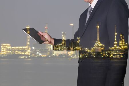 Double exposure of businessman looking the tablet and oil refinery industry plant in the night as Energy and Technology concept.