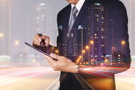 Double exposure of businessman hand hold tablet, light trails on the street, city and urban in the night as business, technology and communication concept.