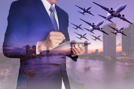 Double exposure of businessman working with tablet, airplane flying, city,urban and river in the night as business, transportation, travel, technology and communication concept.