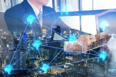 Double exposure of businessman working with table, night cityscape and light blue glowing tech networking world as business, technology, innovation and globalization concept