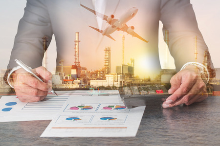 Foto de Double exposure of businessman working with document and calculator for analyze in the work, airplane, fuel, Electric generating factory or plant with sunset as business, industry and energy concept. - Imagen libre de derechos