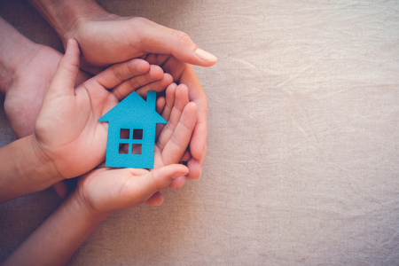 Photo pour Adult and child hands holding paper house, family home and real estate concept - image libre de droit