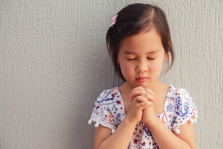 Foto de asian little girl praying with eyes closed - Imagen libre de derechos
