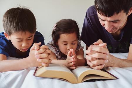 Foto de parent and children praying on the bed, family pray together - Imagen libre de derechos