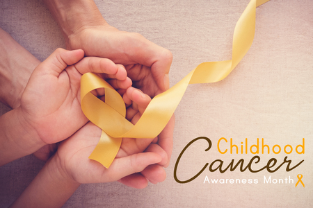 Photo for adult and child hands holding yellow gold ribbon, Childhood cancer Awareness month - Royalty Free Image