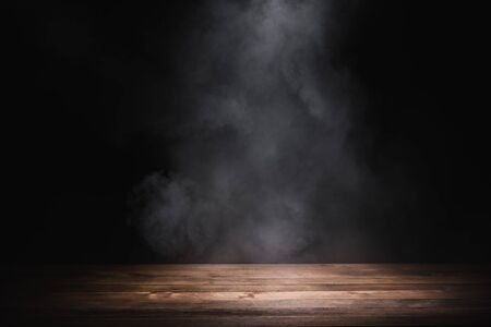Photo for empty wooden table with smoke float up on dark background - Royalty Free Image