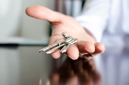 Foto de Estate agent showing house keys on a wooden table - Imagen libre de derechos