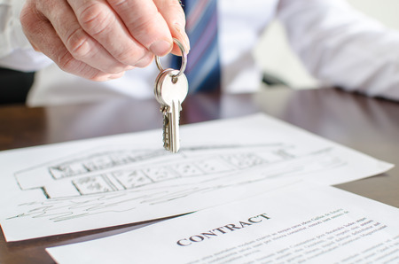 Photo for Estate agent holding house keys over a contract - Royalty Free Image