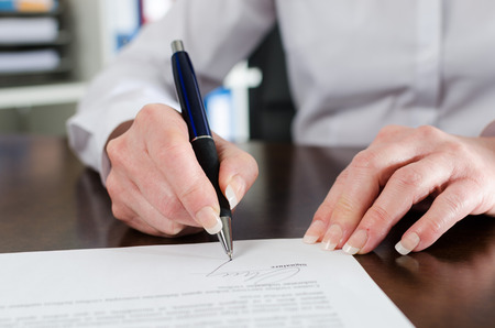 Photo for Businesswoman signing a document at office - Royalty Free Image