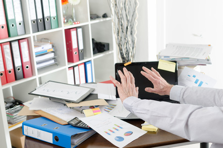 Businessman refusing to see his cluttered desk