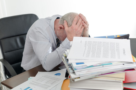 Stressed businessman holding his head in his hands