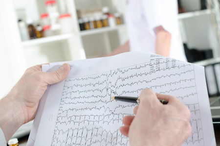 Foto de Doctor analyzing an electrocardiogram in medical office - Imagen libre de derechos