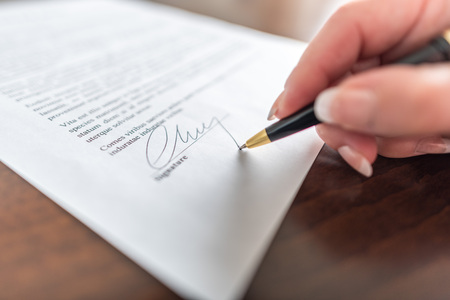 Photo pour Woman hand signing a contract - image libre de droit