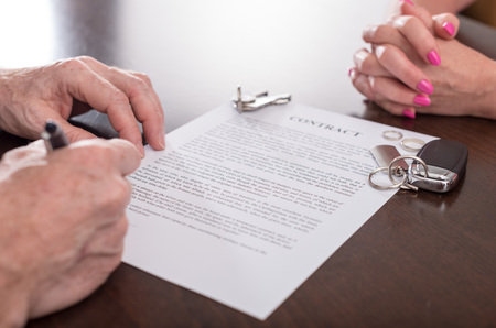 Foto de Husband signing separation contract infront of his wife (random english dummy text used) - Imagen libre de derechos