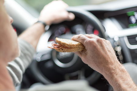 Photo for Man eating a sandwich while driving - Royalty Free Image
