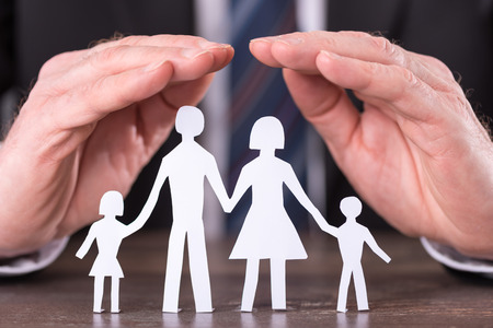 Foto de Concept of family insurance with hands protecting a family - Imagen libre de derechos