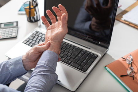 Foto de Businessman suffering from wrist pain in office - Imagen libre de derechos