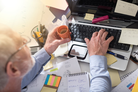 Businessman working on a cluttered and messy desk, top view, light effect