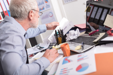 Disorganized businessman looking for documents on his desk