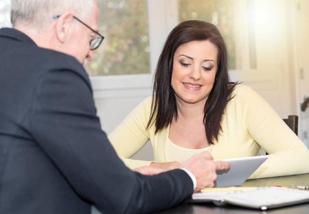 Photo pour Smiling young woman meeting a financial adviser, light effect - image libre de droit