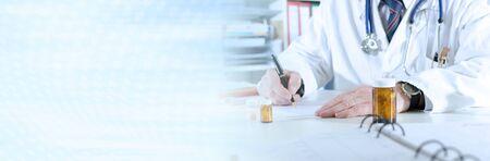 Foto de Doctor writing prescription at medical office; panoramic banner - Imagen libre de derechos