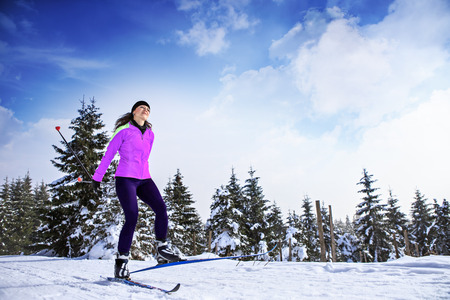 Photo pour A woman cross-country skiing in the wintry forest - image libre de droit