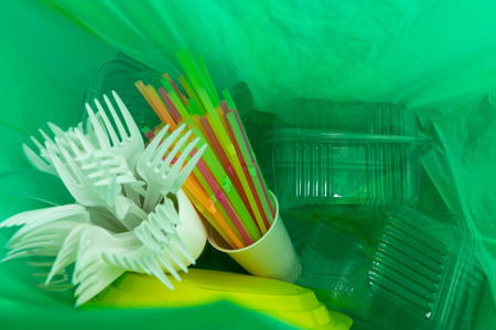 Foto de Inside of green plastic bag with single use cutlery plates straws cup and package boxes as ecology environment waste pollution concept - Imagen libre de derechos