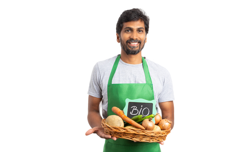 Photo pour Indian hypermarket or supermarket employee with happy exptession holding grocery basket with bio text on sign isoalted on white - image libre de droit