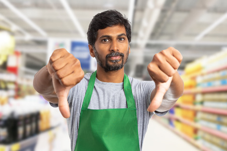 Photo for Indian supermarket or hypermarket employee man making double thumbs-down gesture as dislike concept - Royalty Free Image