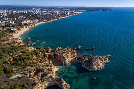 Foto de Aerial view of the coastline with beautiful beaches along the city of Portimao in Algarve, Portugal - Imagen libre de derechos