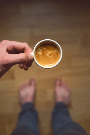 Photo for Young man drinking morning coffee and. Coffee break. Man holding cup of fresh roasted coffee. Top view - Royalty Free Image