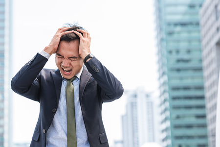 Stressed Asian businessman scream while cover his head with both hands with city in background