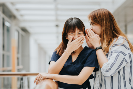 Photo for Young Asian girl whispering gossip or secret to her friend with smile and laugh - Royalty Free Image