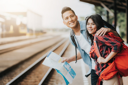 Photo for Happy Asian couple traveler holding a map at train station waiting for train - Royalty Free Image