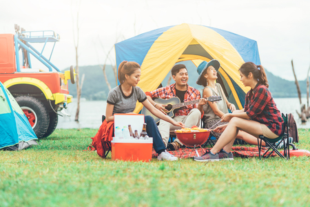 Photo pour Group of Asian friends having fun eating barbecue outdoor while camping and play guitar. - image libre de droit