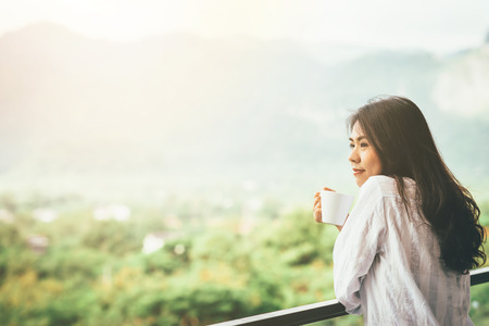 Photo for Asian woman drinking a cup of coffee and enjoy nature view in morining with sunlight - Royalty Free Image