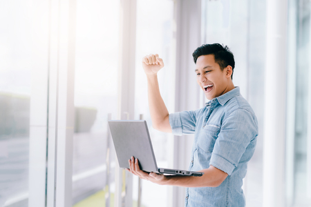 Photo pour Happy excited Asian man holding laptop and raising his arm up to celebrate success or achievement. - image libre de droit